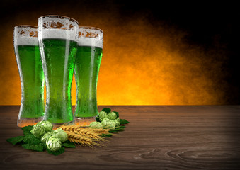 three glasses of green beer with barley and hops. 3D render