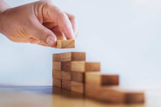 hand stack woods block step on table. business development concept