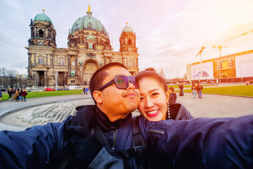 Young Couple Tourists taking selfie with mobile phone in front of Berlin Cathedral (Berliner Dom) in Berlin, Germany