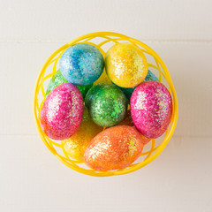 Basket with colorful eggs on a white wooden table. The view from the top.