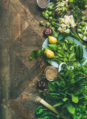 Spring healthy vegan food cooking ingredients. Flat-lay of vegetables, fruit, seeds, sprouts, flowers, greens over wooden background, top view, copy space, vertical composition. Diet food concept
