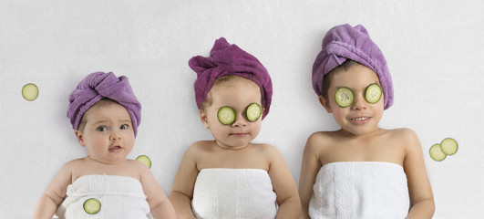 Funny baby girl and kids in white towels and terry cloth bath turbans with cucumber face treatments