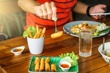 A man eating Por Pieer Tod (Thai Spring Roll ) with fresh vegetable and dipping sauce