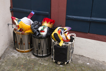 Basel carnival 2018. Pfeffergaesslein, Basel, Switzerland - February 19th, 2018. Close-up of a pile of carnival masks and snare drums in the corner of the street