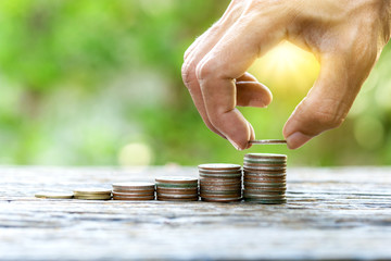 Male hand putting money coin of stack growing business to saving money concept on soft light nature background.