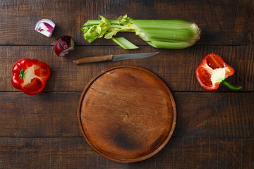 Round wooden kitchen board fresh vegetables wooden table top view