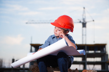 pensive handsome little kid in helmet solves problem of project on construction site with building crane and building in the background