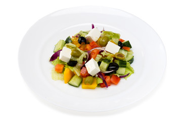 Greek salad in a white plate on a white background
