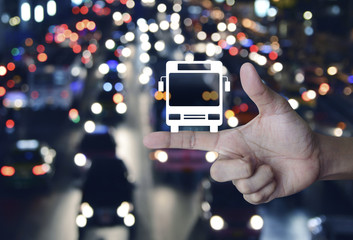 Bus flat icon on finger over blur colorful night light city with cars, Business transportation service concept
