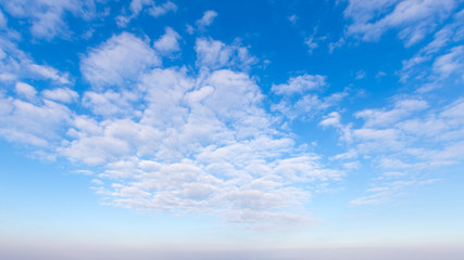 Blue sky with clouds, for backgrounds or textures.
