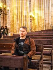 Blond man sitting in a Catholic Church