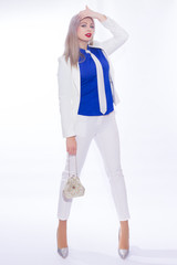 Studio portrait in full length of a beautiful young blond woman with long hair in a white pants suit. A girl in silvery shoes with high heels, in her hands she holds a small silver handbag