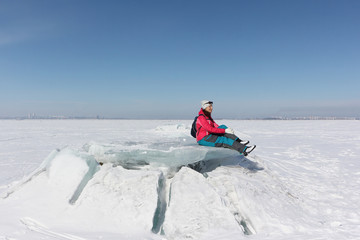 Happy woman in a red jacket sitting on an ice floe on a frozen river, Ob reservoir, Russia