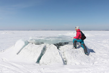 Happy woman in a red jacket stepping on an ice floe on a frozen river, Ob reservoir, Russia