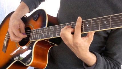 Guitarist performance barre on acoustic guitar correctly clamp chord etalon game mediator close-up