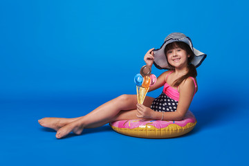 Pretty little girl swimsuit,beach hat sitting on inflatable ring relaxation. Fashionable little lady smile. Happy child in studio,blue background like sea water. Concept summer vacation, travel.
