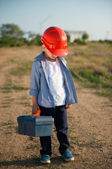 sad little working kid in orange helmet hung his head with tool case in one hand standing on path