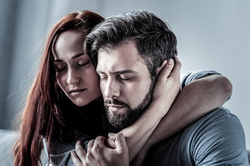 Love you so much. Redhead satisfied young woman hugging her husband closing her eyes spending time together.
