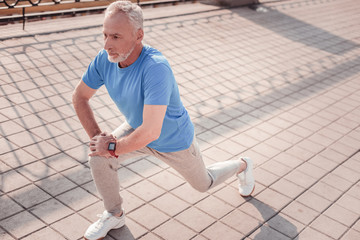 I can. Serious aged focused man preparing for the training looking straight making stretch exercises.