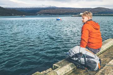 Traveler man sits on the mountain lake pier