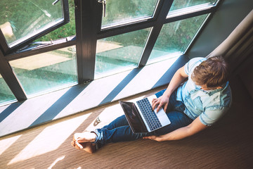 Man works with laptop sitting on the floor near the open window