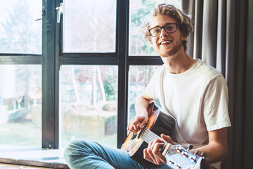 Happy smiling young man play on guitar near the window
