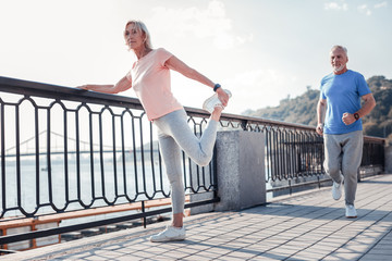 Dont stop. Senior pleasant sporting couple spending time together being on fresh air and having training on the quay.