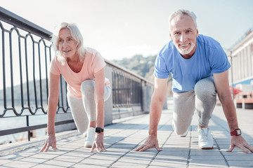 Who will win. Confident friendly aged couple preparing to run across the quay looking straight and touching to the ground. Wall mural