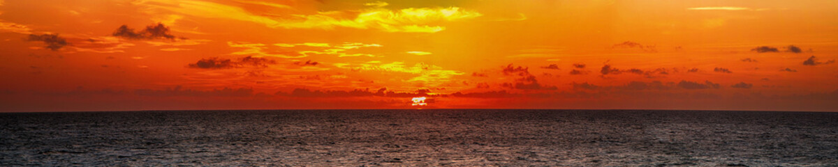 Beautiful panorama of a bright sunset in the ocean
