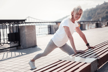 I can do this. Pleasant confident aged woman doing exercises relying on the bench being on the quay.