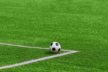 A soccer ball framed by white corner markings on a green football field.