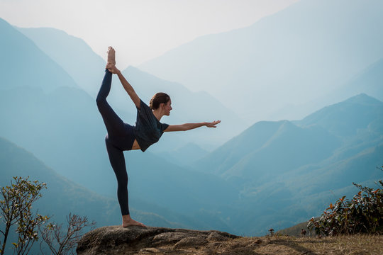 Young woman practices yoga on mountain cliff at sunrise. Mountanious landscape