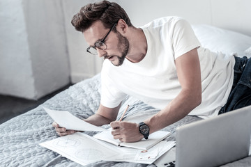 True workaholic. Smart handsome serious man looking at his schemes and taking notes while working at home