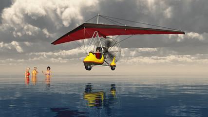 Ultraleichtflugzeug über dem Meer mit badenden Frauen