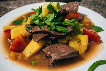 stewed meat with potatoes and vegetables on a plate