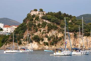 Yachts sail near a fortress on a hill Parga Greece summer season
