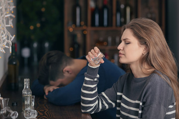 Young woman drinking near unconscious drunk man in bar. Alcoholism problem