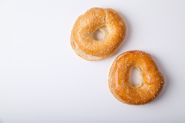 Two fresh baked bagle buns with sesame seeds on white background pre-cut for making sandwiches