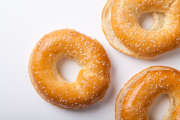 Three fresh baked bagle buns with sesame seeds on white background pre-cut for making sandwiches