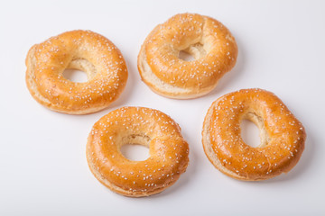 Four fresh baked bagle buns with sesame seeds on white background pre-cut for making sandwiches