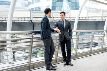 Asian businessmen talking together on a day break outdoors