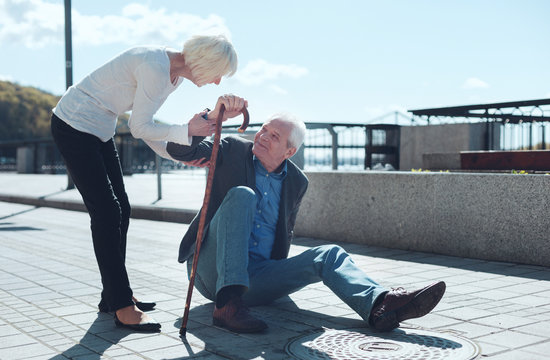 Let me help you. Loving wife giving her husband to lean on her after falling to the ground during a daily promenade.
