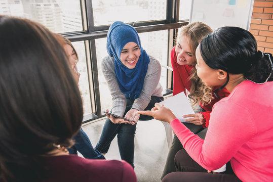 Women sitting in circle enjoying sharing stories in group meeting
