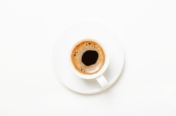 White cup of black coffee espresso with foam, white background, top view