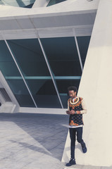 man dressed in african clothes consults his smartphone in a modern building