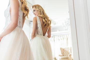 Stylish bride in lace dress by mirror in wedding salon