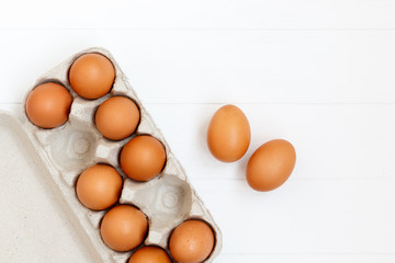 fresh or raw brown eggs on white wooden background, top view, flat lay with copy space, food ingredient