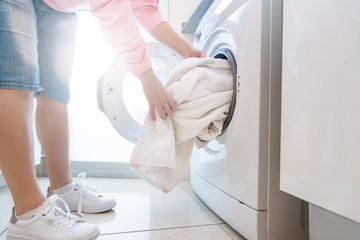 Woman puting dirty laundry into washing mashine