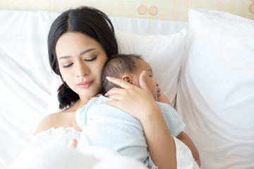 Portrait of Mother and new born baby on a white bed.