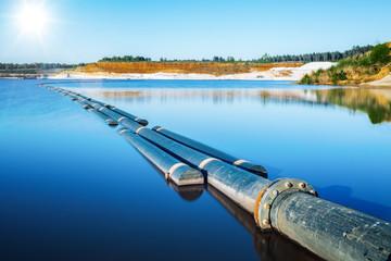 Pipeline in blauem See in Tagebau